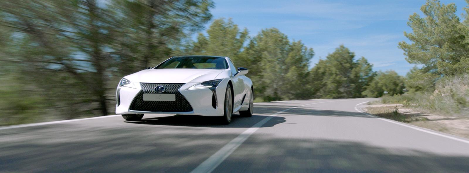 Vista frontale laterale della nuova LC colore bianco F Sport che sfreccia ad alta velocità su strada