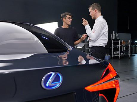 Retro della concept car LF FC con logo Lexus illuminato e sullo sfondo i due designer dello studio Formafantasma