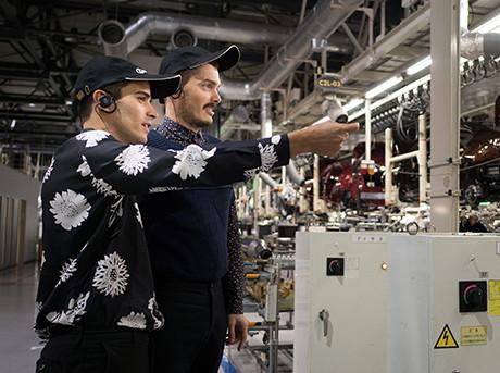 I due designer dello studio Formafantasma intenti ad indicare una catena di montaggio