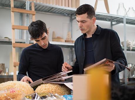 Due ragazzi intenti a guardare un catalogo sullo sfondo una scala in legno