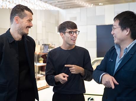 Tre ragazzi che parlano e sorridono sullo sfondo il cofano di un auto con logo Lexus