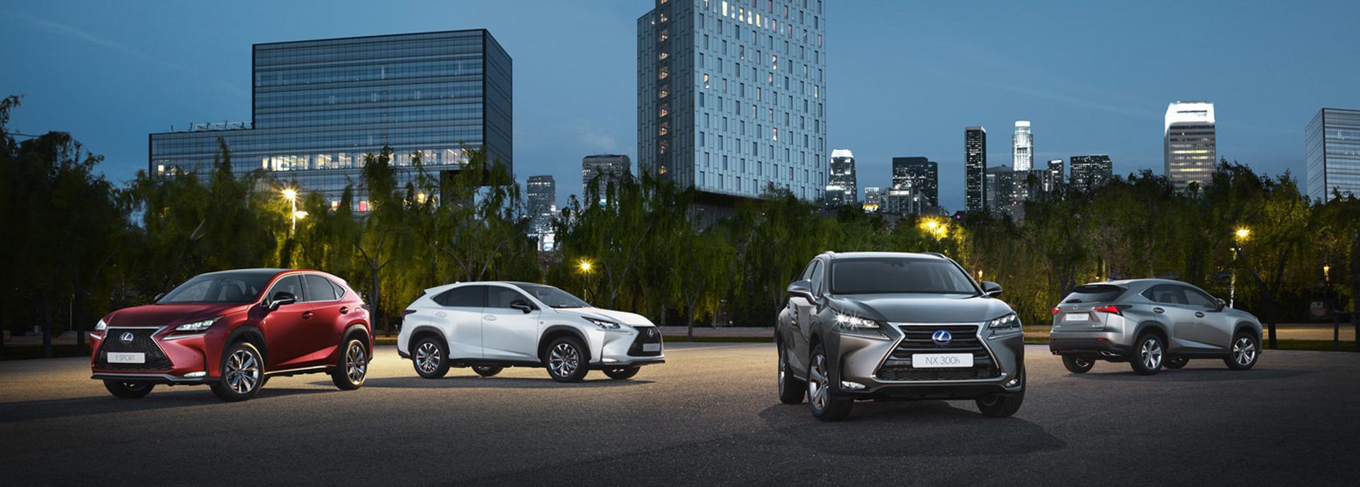 Quattro SUV Lexus NX Hybrid in un parcheggio di sera con grattacieli sullo sfondo