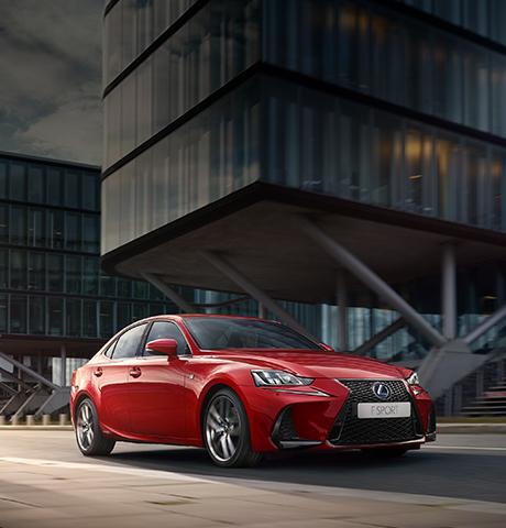 Nuova IS Hybrid F SPORT colore rosso brillante percorre una strada con edifici moderni sullo sfondo