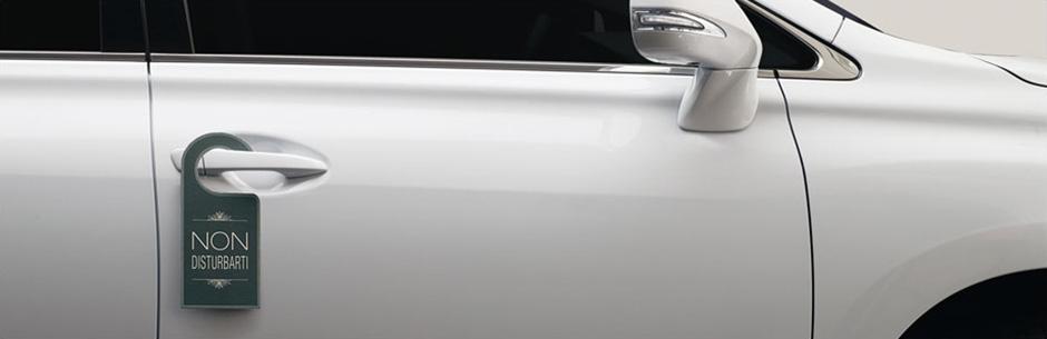Vista laterale del SUV Lexus Hybrid con cartellino non disturbare sulla maniglia della portiera