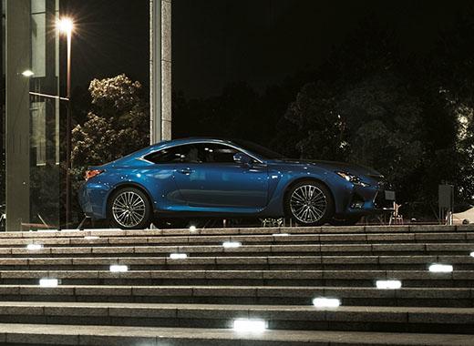 Fiancata della RC F colore blu e cerchi in lega da 19 pollici di sera in cima ad una scalinata