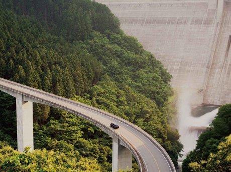 Auto che percorre un ponte e sullo sfondo una diga