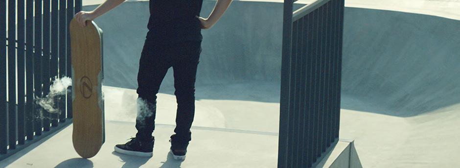 Le gambe di uno skater in posa mentre regge l hoverboard Lexus in verticale sulla sua destra