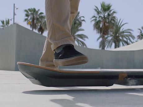 Dettaglio piedi su hoverboard con pantaloni beige e scarpe nere
