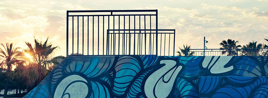 Struttura per praticare skating dipinta con murales astratti sullo sfondo cielo sereno e palme