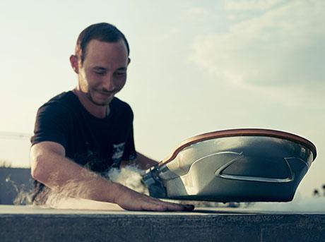 Un ragazzo posiziona la sua mano destra tra il pavimento e l hoverboard Lexus
