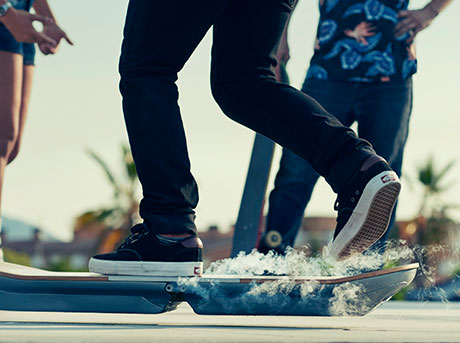 Dettaglio piedi ragazzo su hoverboard che lievita in aria emettendo vapore