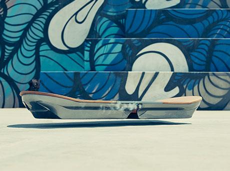 Vista diagonale frontale dell hoverboard davanti ad una parete dipinta con murales