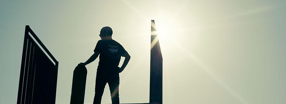 Sagoma di un ragazzo di spalle e di un hoverboard con sfondo cielo soleggiato