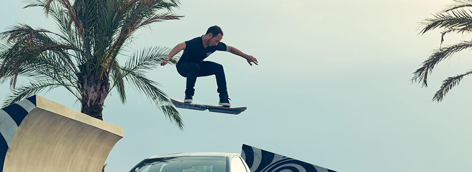 Ragazzo su hoverboard mentre supera un auto con un salto