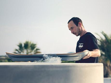 Un ragazzo regge l hoverboard che lievita su di un piano emettendo vapore