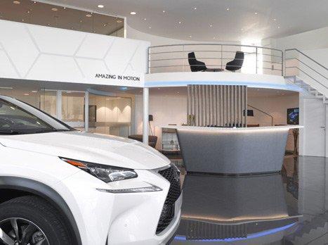 Parte frontale di un NX Hybrid bianco nella sala di accoglienza di uno showroom Lexus