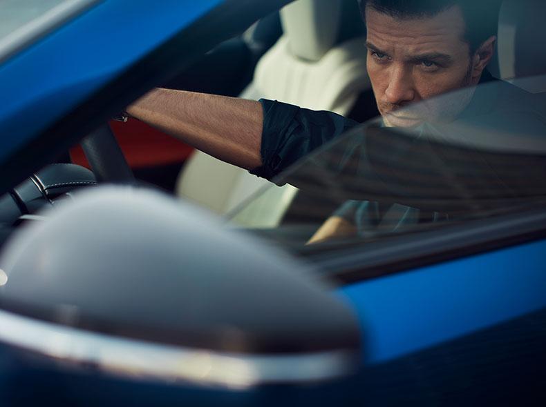 Een man achter het stuur van een blauwe Lexus LC 500h