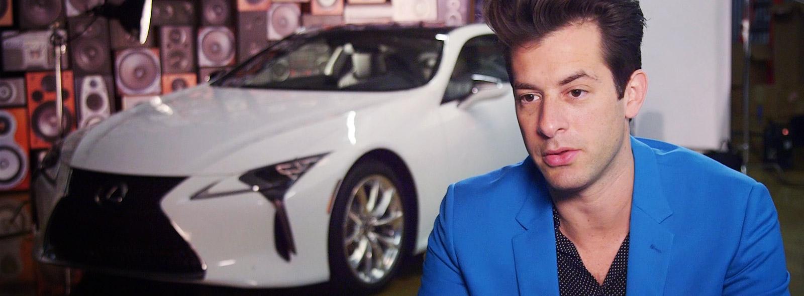 Muziekproducent Mark Ronson zittend op de voorgrond in blauw pak met op de achtergrond een witte Lexus LC driekwart van voren gezien in het kader van de campagne Make Your Mark