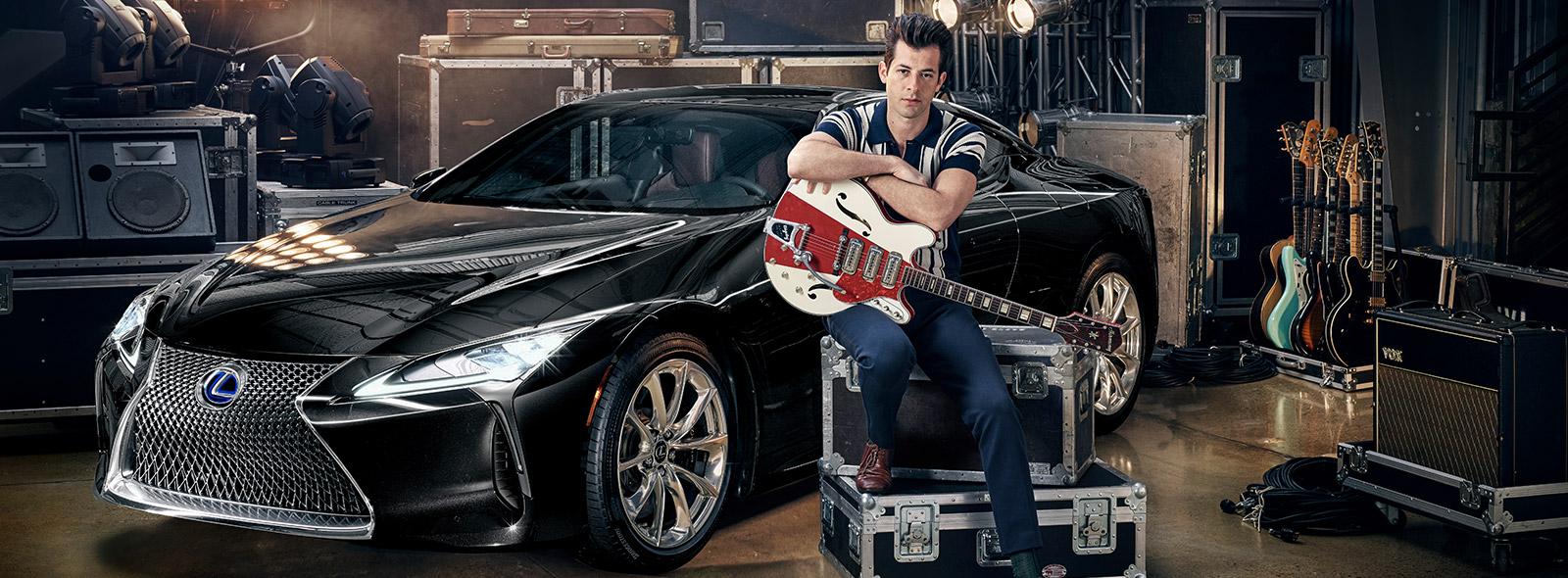 Internationaal gevierde muziekproducent Mark Ronson zittend met een wit rode gitaar voor een zwarte Lexus LC driekwart van voren gezien