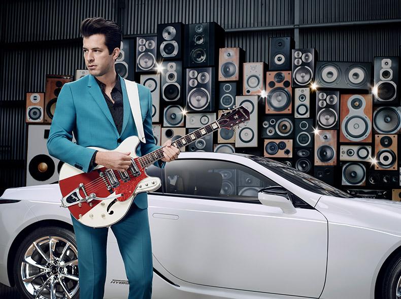 Muziekproducent Mark Ronson staand in blauw pak met een wit rode gitaar kijkend naar links voor een witte Lexus LC bekeken vanaf de zijkant in het kader van de campagne Make Your Mark