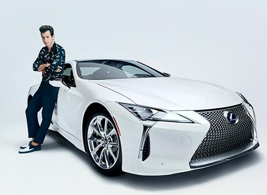 Muziekproducent Mark Ronson staand tegen een witte Lexus LC driekwart van voren gezien in het kader van de campagne Make Your Mark