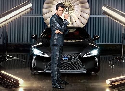 Muziekproducent Mark Ronson staand naar rechts in donker pak tegen een zwarte Lexus LC direct van voren gezien in het kader van de campagne Make Your Mark