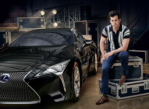 Muziekproducent Mark Ronson zittend naast een zwarte Lexus LC driekwart van voren gezien in het kader van de campagne Make Your Mark