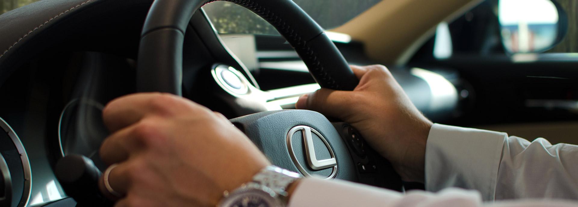 Zakenman met een Lexus stuur in zijn handen