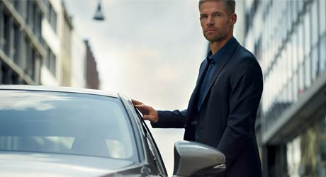 Een stilstaande grijze Lexus IS 300h met zakenman