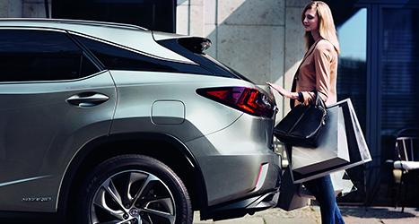 Vrouw opent achterbak van een Lexus