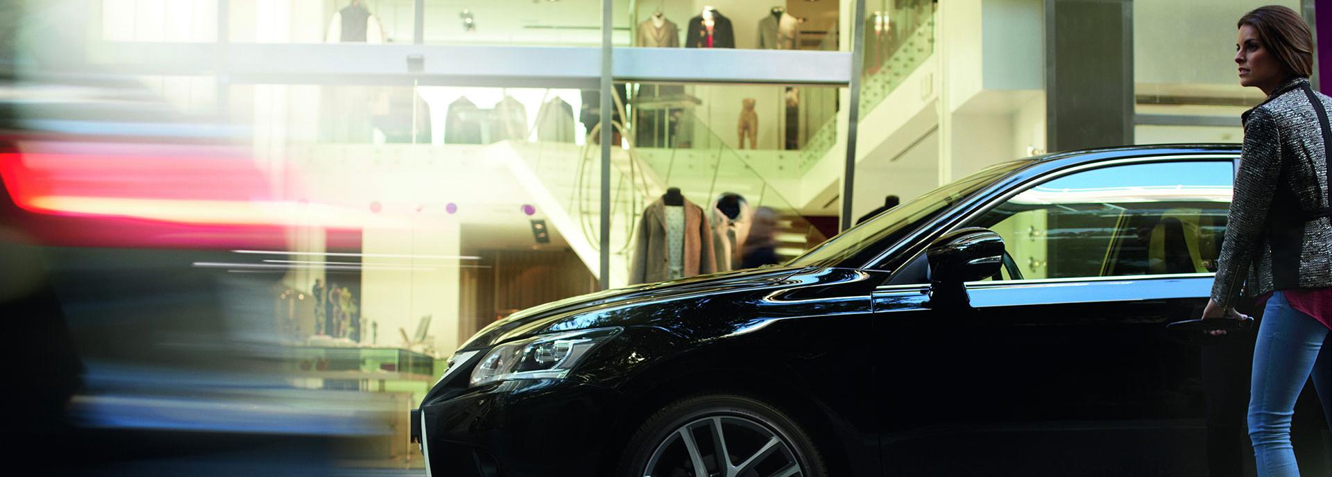 Vrouw staat naast zwart Lexus CT