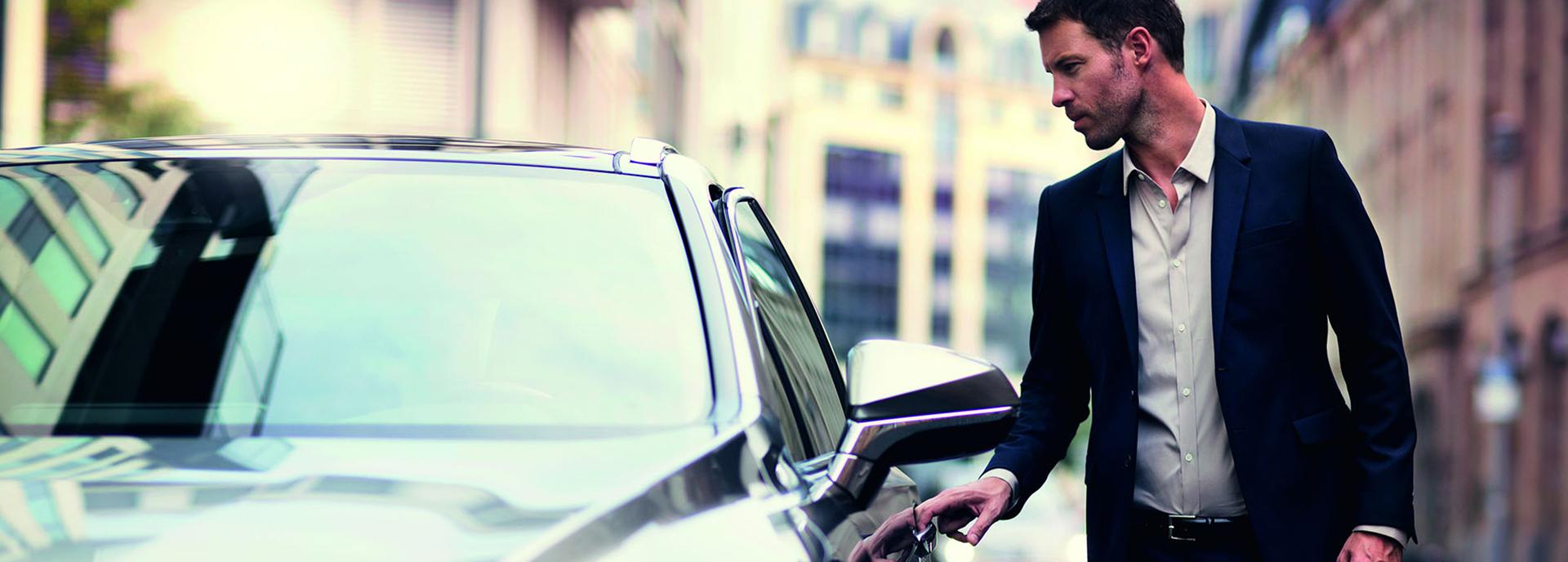man in net pak opent deur Lexus