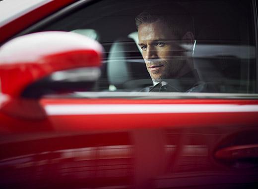 Een man in een rode Lexus IS 300h