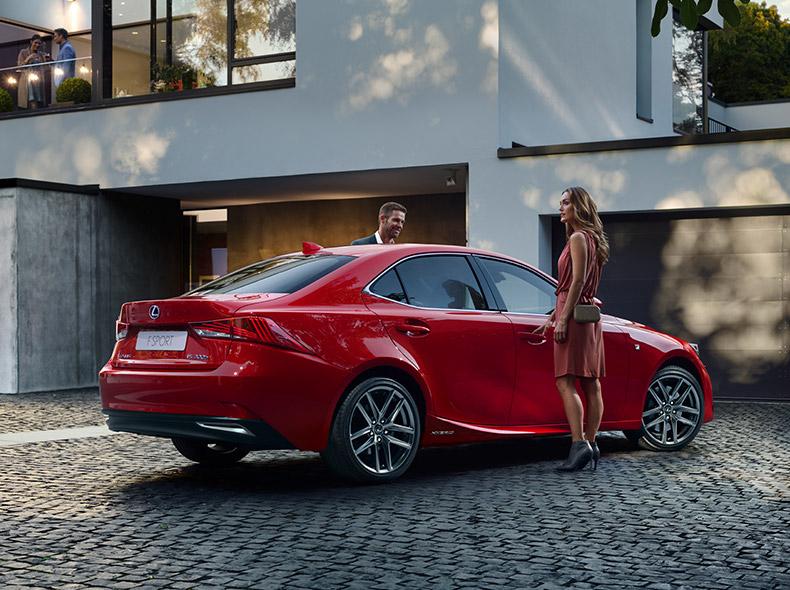 Een man en een vrouw stappen in een rode Lexus IS 300h