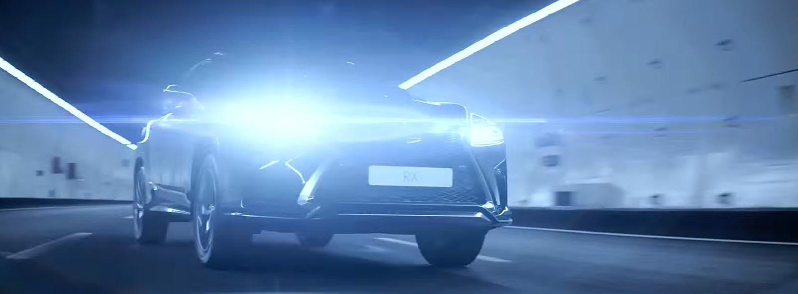 Vooraanzicht van rijdende Lexus RX met koplampen aan
