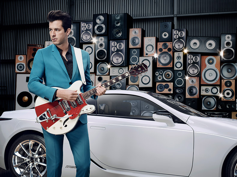 Mark Ronson med gitarr framför vit Lexus LC 500h