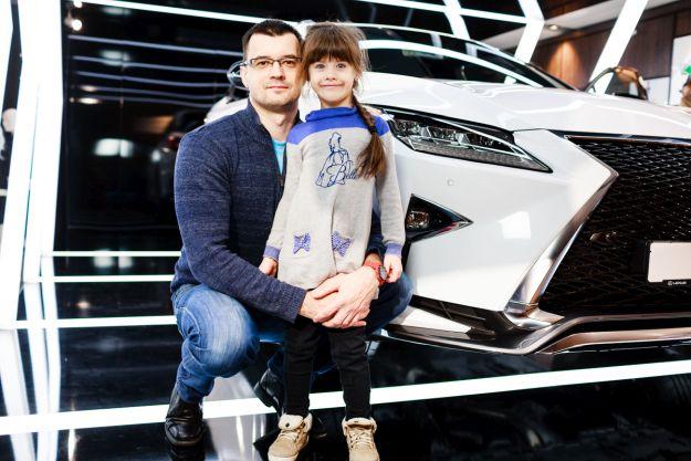 Батько з донькою поруч з Lexus
