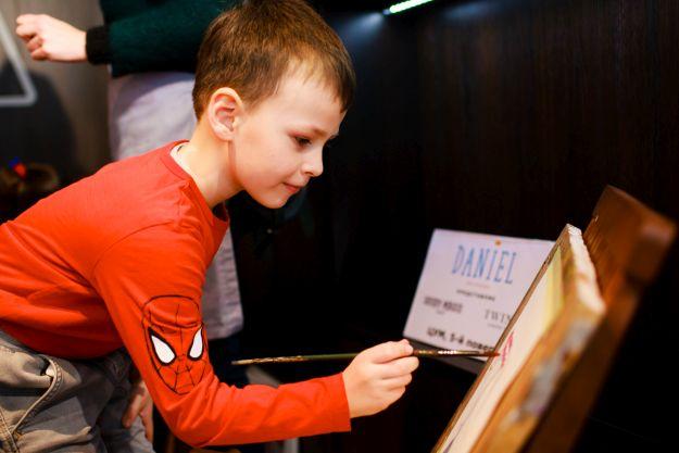 Хлопчик малює пензлем
